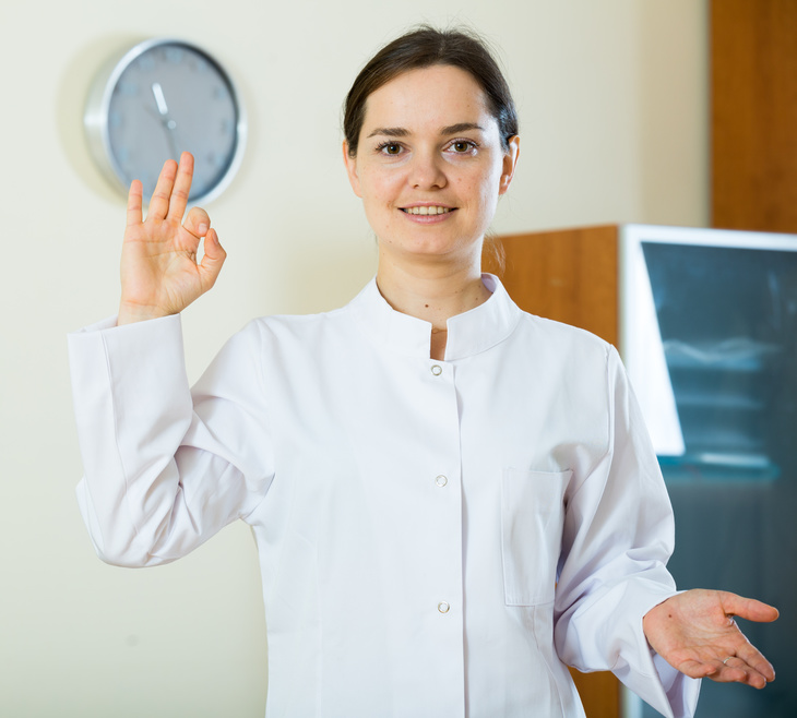 Portrait of professional female brunette doctor smiling in clinic